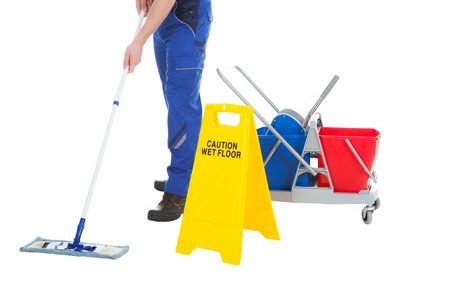 Person mopping floor with caution sign and buckets
